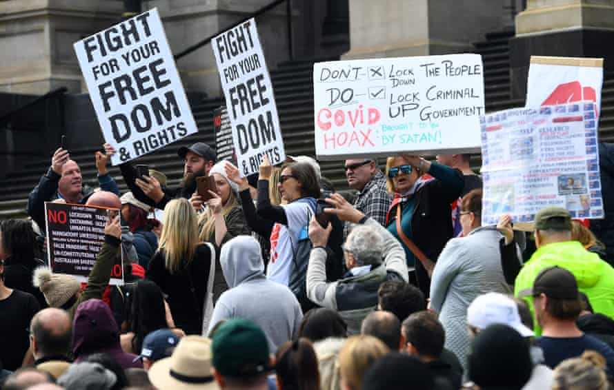 Anti-lockdown protesters hold placards on the steps of Victoria's state parliament in Melbourne on May 10, 2020.