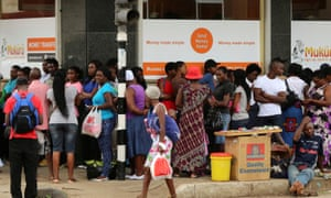 People queue to withdraw money from a bank in Harare