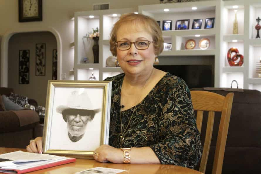 Arlinda Valencia poses at her home in El Paso in April, with a portrait of her great-grandfather, Longino Flores, killed in the Porvenir massacre.