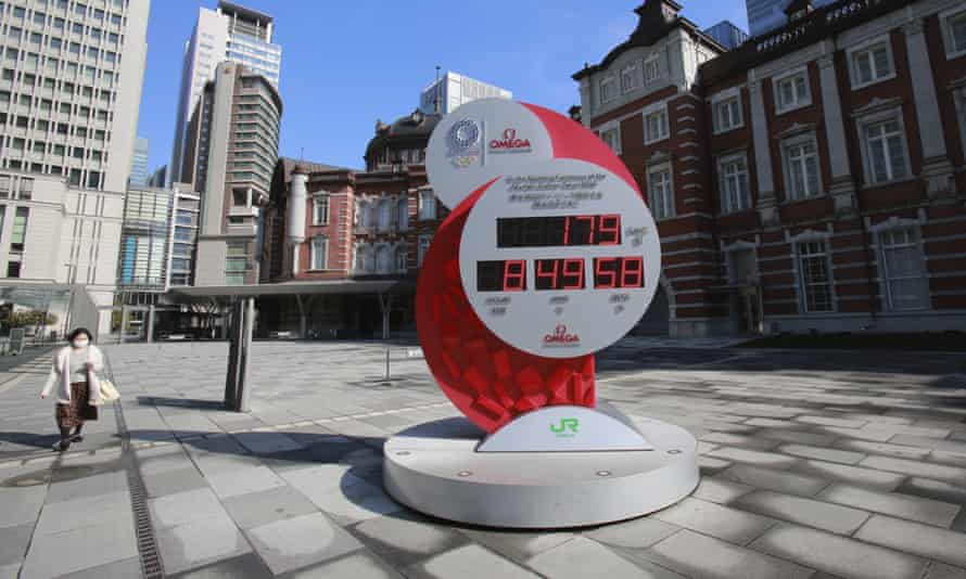A woman walks past a Tokyo Olympic and Paralympic Games countdown clock at Tokyo station