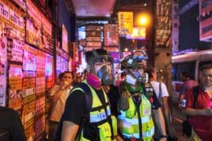 Marvel and friend wear respirators after police shot pepper balls, in Mongkok, Hong Kong.