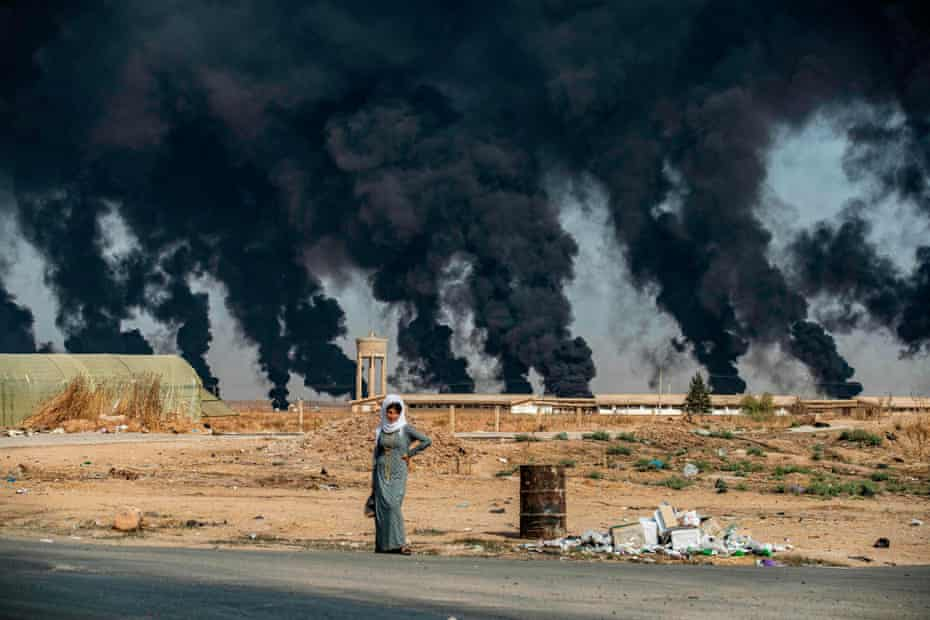 A woman stands on the side of a road on the outskirts of Tal Tamr, near the Syrian Kurdish town of Ras al-Ain