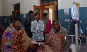 Two men who consumed bootleg alcohol sit on a hospital bed as relatives look on, in Saharanpur, Uttar Pradesh.
