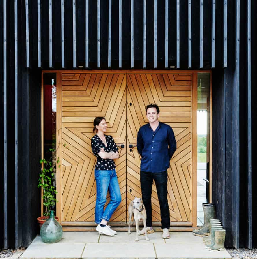 Lucy Kent and John Gilbey and their dog outside their star-shaped front door.