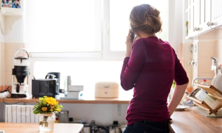 A young woman at home in the kitchen is using a telephone