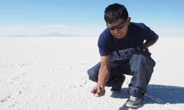 Angel Calani dips his finger into the crusted earth to show the lithium brine beneath