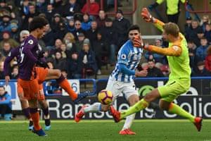 Sane shoots past Lossl to score City's third goal.