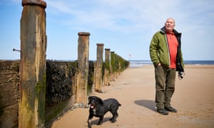 Former steelworker Brian Dennis on the beach with his cocker spaniel Darcy.