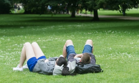 People sit in the sun in St James's Park, London.