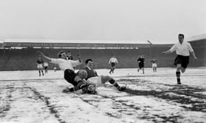 Birmingham City's Jeff Hall (centre) slides in to make a tackle on West Bromwich Albion's Ray Barlow on a snowy Hawthorns surface