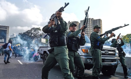 Members of the Bolivarian national guard who joined the self-proclaimed acting president Juan Guaidó fire into the air near La Carlota military base in Caracas on Tuesday.