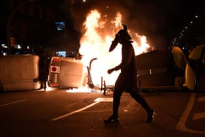A protester walks past burning rubbish containers during clashes with the Catalan police force after a demonstration last week in Barcelona