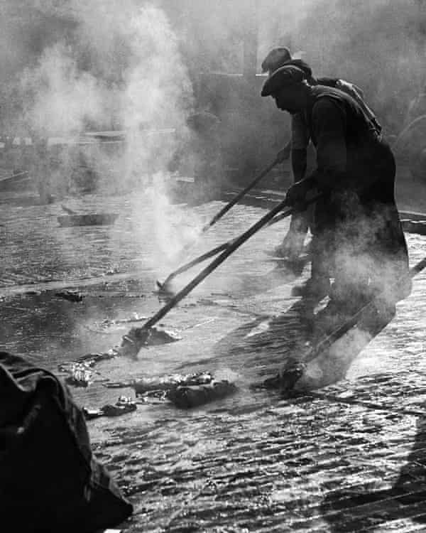 An image by Wolfgang Suschitzky of workers applying asphalt to the surface of Charing Cross Road, London, in the 1930s