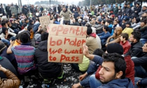 Refugees hold banners during a protest demanding the opening of the borders.