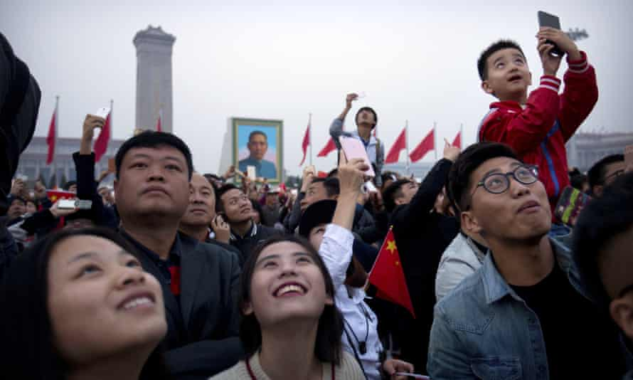 People watch a flock of birds that was released after the dawn flag-raising ceremony at Tiananmen Square on National Day in Beijing on Saturday.