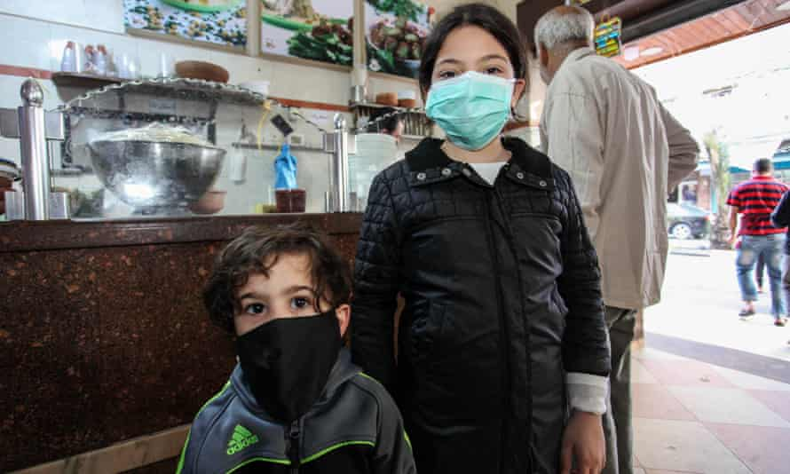 Palestinian children wearing protective face masks