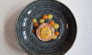 Steak tartare on a round blue plate with egg yolk on top and Gentleman's Relish dotted around the plate
