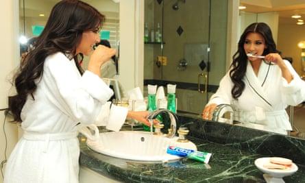 Kim Kardashian menggosok giginya dalam sebuah adegan untuk Keeping Up with the Kardashians, 2009.