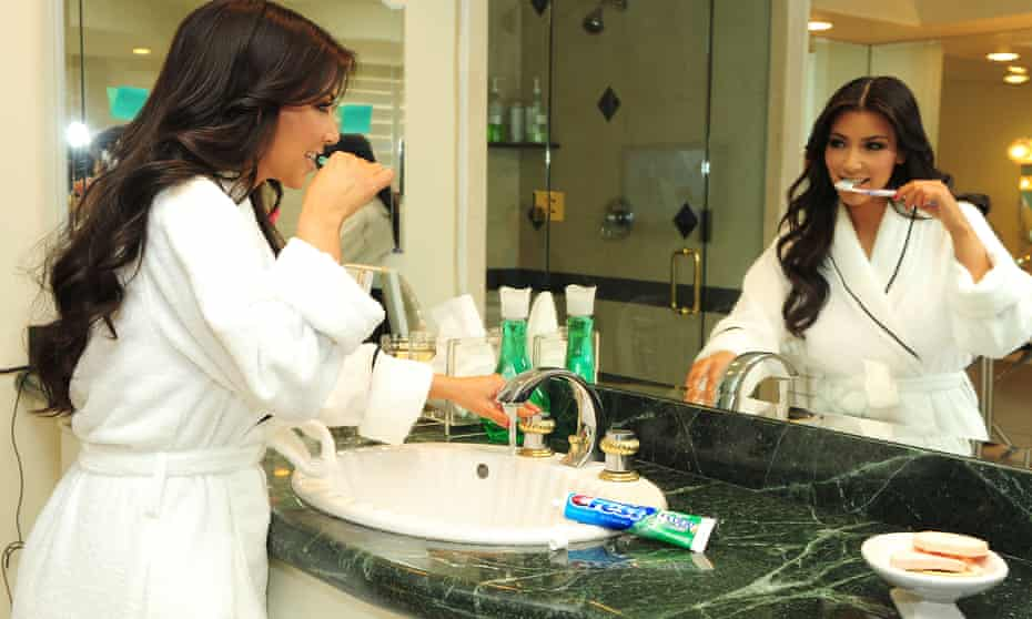 Kim Kardashian brushing her teeth in a scene for Keeping Up with the Kardashians, 2009.
