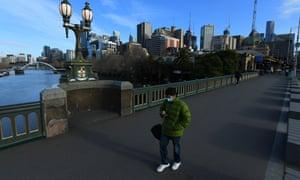 A person wearing a face mask walks across Princes Bridge in Melbourne