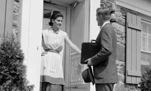 A black and white picture from the 1950s showing a door-to-door salesman talking to a woman.