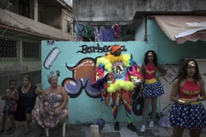 A 'bate-bola', centre, stands next to people wearing Wonder Woman costumes during carnival festivities at the Cidade de Deus, or City of God, favela