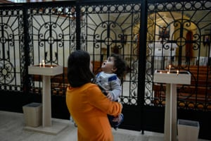 Inside the Armenian church at Vakıflı, mother and baby standing at grille in front of the altar.