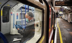 Man wearing a face mask and gloves sitting on a commuter train in London