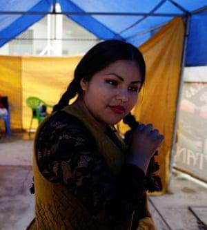 Susana La Bonita, a cholita wrestler, fixes her hair before their fight.