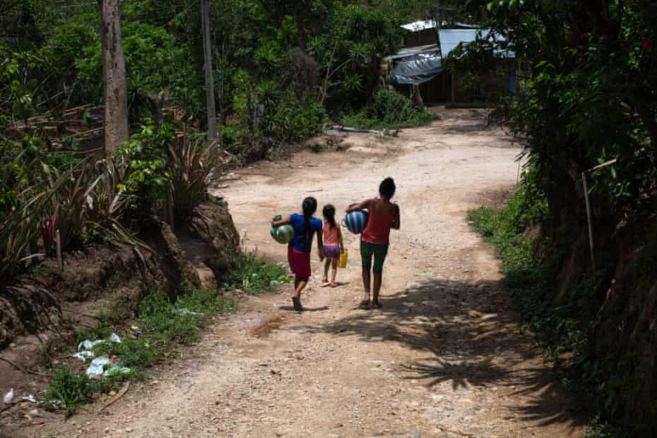 Girls carry water jugs after filling them in a nearby stream in Tizamarte, Camotán, Chiquimula, Guatemala.