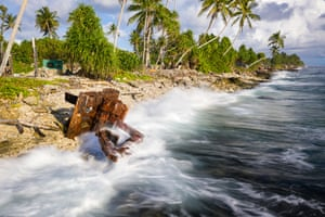 An earth mover lies abandoned amid the waves of the Pacific Ocean in Funafuti