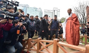 Han Sang-Gyun, second from right, walks with a Buddhist monk as they exit the Jogye Temple in Seoul to avert a police raid.