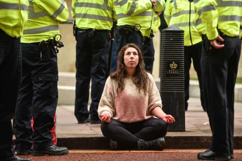 A climate change activist is surrounded by police officers outside the Treasury building this month.