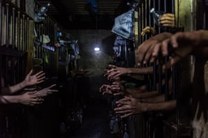 Prisoners beg for food and water at their cells in a police station. Many said they had regular jobs but turned to crime because of the impossibility of bringing food home