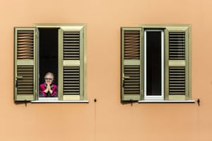 Rome, Italy A woman watching a mass held on the rooftop of the San Gabriele dell'Addolorata neighbourhood during the coronavirus outbreak