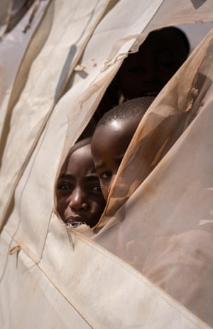 Nyarushishi, Rwanda: children look out of a tent at a transit centre