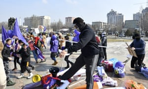 Masked Kyrgyz nationalists attack women's rights activists during the celebration of the International Women's Day at Victory Square in Bishkek, Kyrgyzstan, Sunday, March 8, 2020.