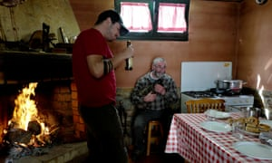 After lighting the fire, Jose Martinez, 31, and his uncle enjoy a break before lunch at their home in Spain's Galicia region in Xinzo de Limia, Spain