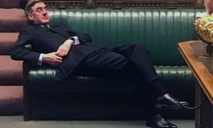 Jacob Rees-Mogg lounges in the Commons in his trademark ill-fitting suit.