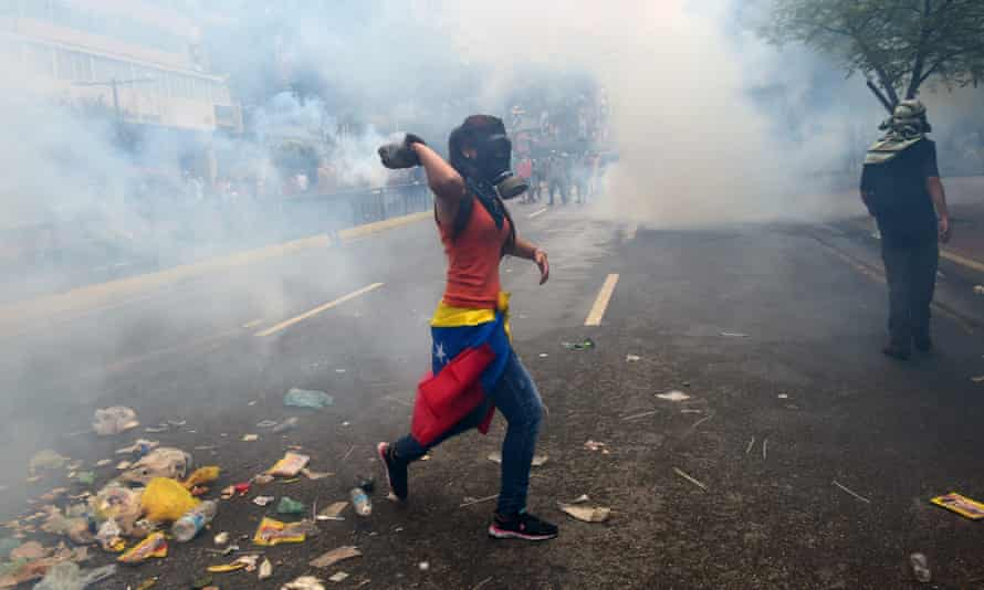 Demonstrators clash with the riot police during a protest in Caracas on Thursday.