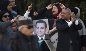 Supporters of Hosni Mubarak hold posters of the former leader as they celebrate his acquittal.