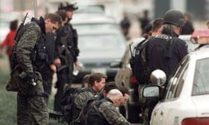 Members of a police SWAT team take a break in front of Columbine High School, after the shooting stopped.