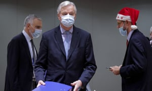 European Union chief negotiator Michel Barnier, centre, carries a binder of the Brexit trade deal during a meeting at the European Council building in Brussels.