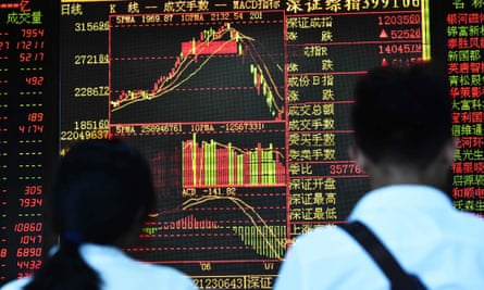 Investors look through stock information at a securities firm in Haikou, Hainan province, on Friday.