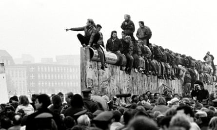 East and West German people celebrate the end of cold war on top of the Berlin Wall, 10 November 1989.