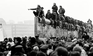 East and West German people celebrate the end of cold war on top of the Berlin Wall, East Berlin, Germany 10 Nov 1989