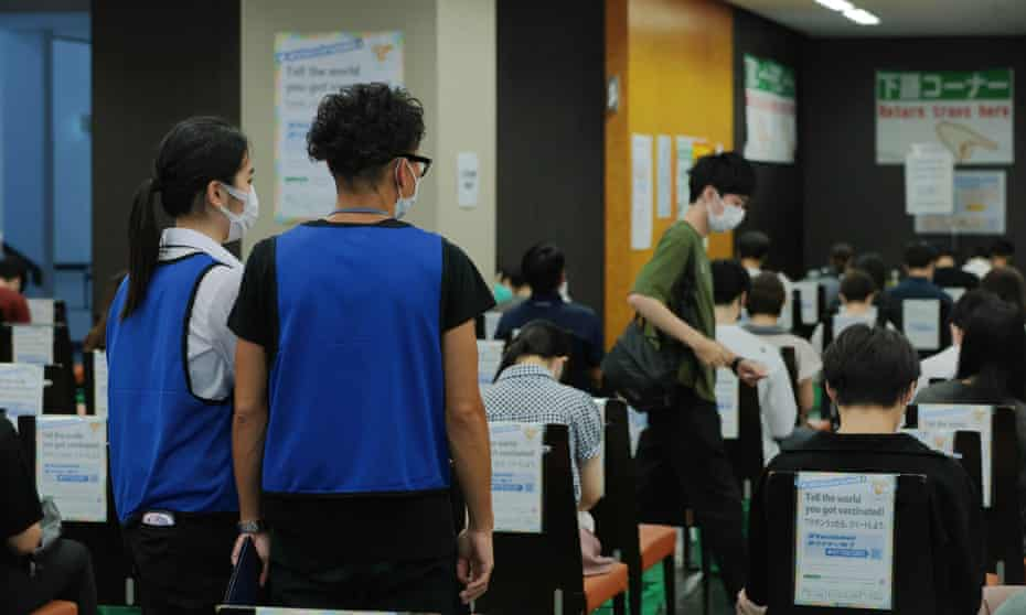Staff at a Covid-19 vaccination centre at Tokyo look over a post-jab waiting room