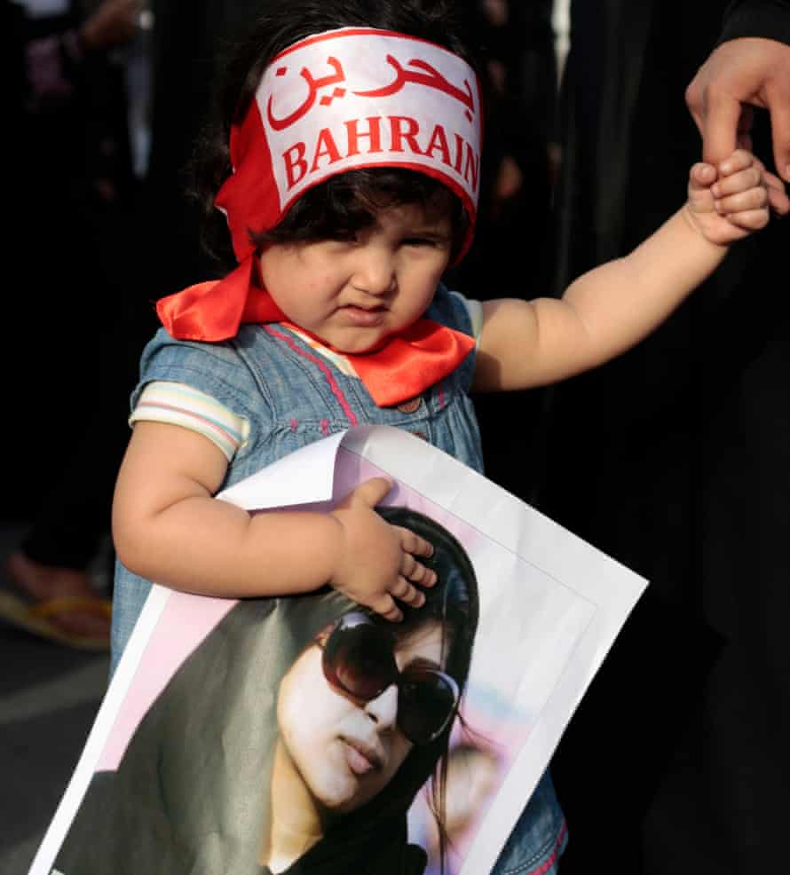 "A girl wearing a headband that reads ""Bahrain"" in English and Arabic holds a poster of jailed opposition human rights activist Zainab al-Khawaja"