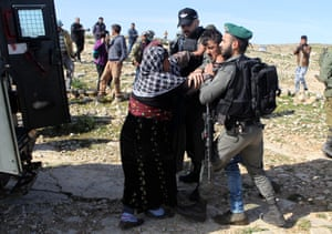 West Bank. Palestinian women attempt to free a detained relative from being taken by the Israeli military during a dispute over the demolition of housing in the village of Tuba near the city of Yatta
