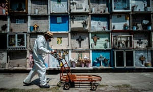 A worker pushes a cart by graves in Ciudad Nezahualcoyotl, Mexico state, Mexico, on 16 May 2020.